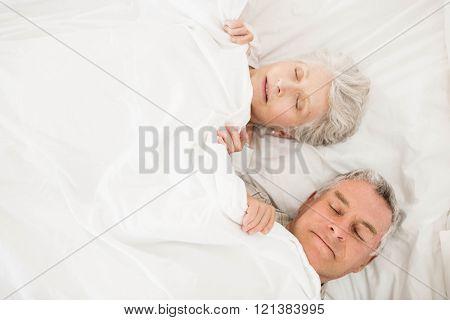 Senior couple sleeping in bed under blanket