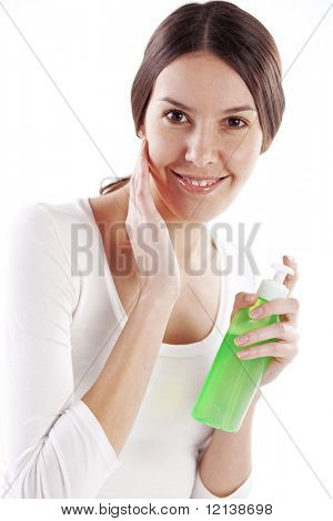 Portrait of beautiful young woman applying face cosmetic products on her skin