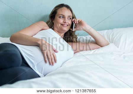 Pregnant woman making a phone call on her bed