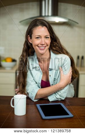 Young woman smiling in kitchen with coffee mug and digital tablet on worktop