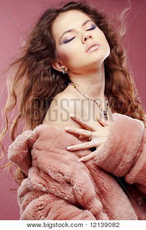 Fashion girl wearing winter fur coat posing over pink