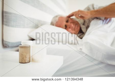 Pillboxes kept on a side table near bed and frustrated senior man in background