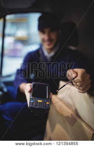 Delivery driver holding device to camera with parcels on seat