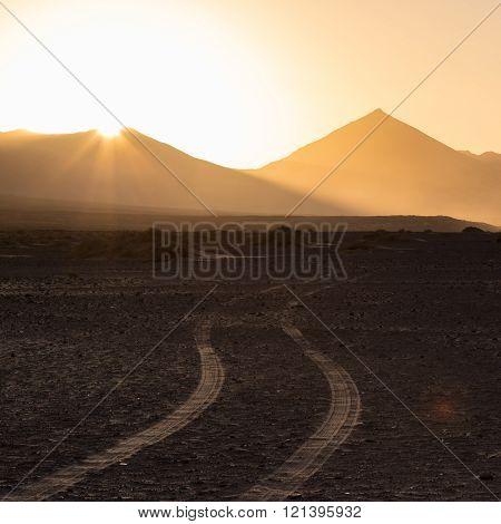 Wheel tracks in sand in dramatic landscape.