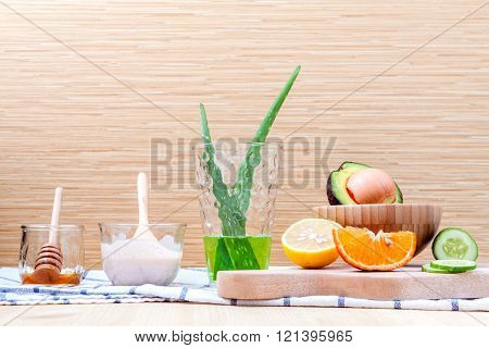 Homemade skin care and body scrub with natural ingredients set up on on  wooden background.