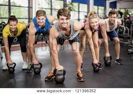 Fitness class lifting dumbbells in gym