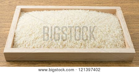 Cuisine and Food Uncooked White Long Rice Basmati Rice or Thai Jasmine Rice in Wooden Tray.