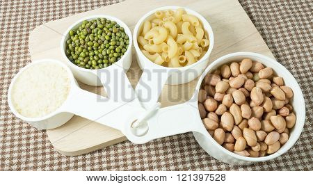 Foods High in Carbohydrate Raw Pasta Rice Peanuts and Mung Beans in Plastic Measuring Cups.