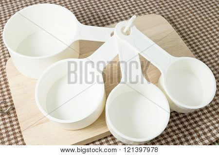 Kitchen Tools and Equipment Four Plastic Measuring Cups in Different Sizes on Wooden Cutting Board.