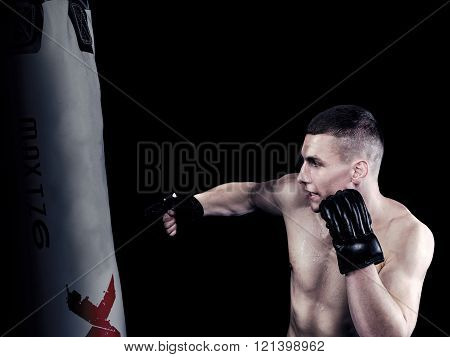 Young man hits punching bag on black background