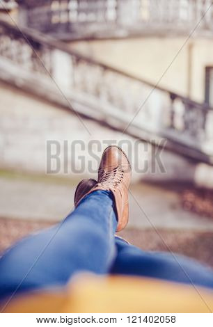 Woman lying on a wall relaxing with jeans and boots