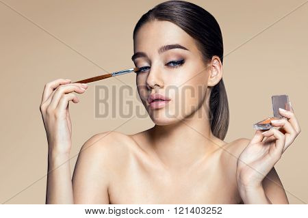 Fascinating young girl with brush for eyeshadow