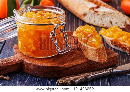 Orange (tangerine) Jam In A Glass Jar On The Table.