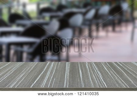 Empty Wooden Table With Black Rattan Table And Chair On The Terrace Blur Background
