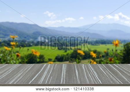 Empty Wooden Table With Flowerbed With Mountain And Paddy View Blur Background