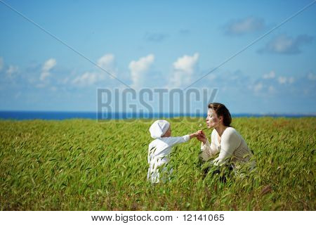 Mother walking with her baby in spring green field