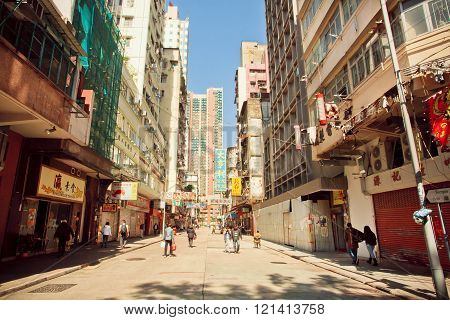 HONG KONG, CHINA - FEB 7: People walking on sunny street with tall concrete buildings in busy district of asian city on February 7, 2016. There are 1223 skyscrapers in Hong Kong.