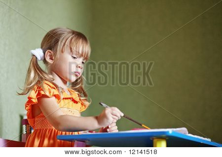Cute girl draw diligently at home