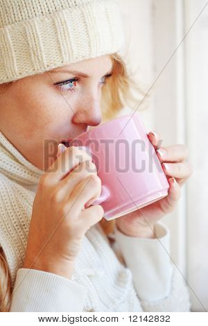Young beautiful woman wearing winter clothing drinking hot coffee