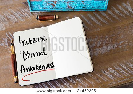 Retro effect and toned image of a fountain pen on a notebook. Handwritten text Increase Brand Awareness as business concept image