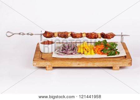 kebab skewers of meat beef on a stick on a board with side dishes cabbage onions