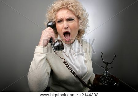 a senior woman with a screaming expression at the telephone