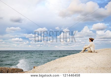 Young Woman Sitting On The Beach Looking At The Sea And Sky
