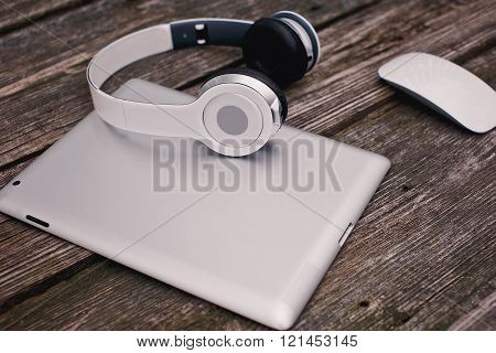 Tablet Computer With Headphones And Mouse Against Wooden Background