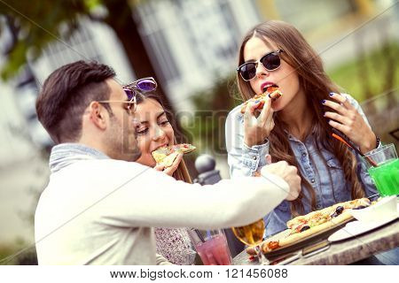 Close-up of three young cheerful people eating pizza and drinking beer outdoors. They are laughing and eating pizza and having a great time.