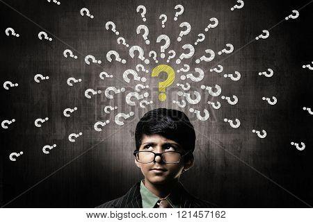 Confused Little Boy Wearing Glasses, Thinking Near Chalkboard
