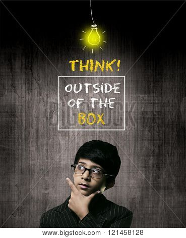 Cute Intelligent Little Boy Wearing Glasses Hand Under Chin And Thinking While Standing Before A Chalkboard. Thinking Outside Of The Box And A Bulb Of Idea Is Hanging