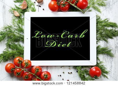 Low-Carb Diet on tablet pc screen with fresh herbs and vegetables on wooden background