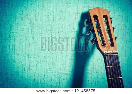 Classical guitar on wallpaper background close-up
