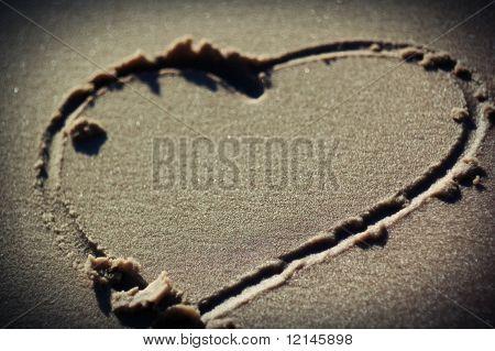 Corazón dibujado en la arena en la playa, vista elevada
