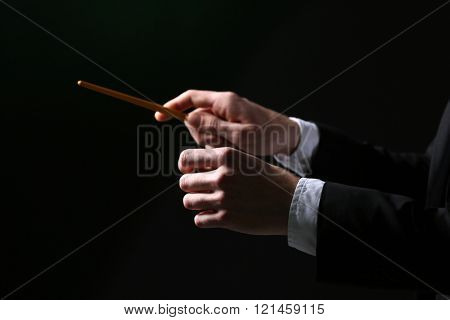 Music conductor directing with baton on black background, close up