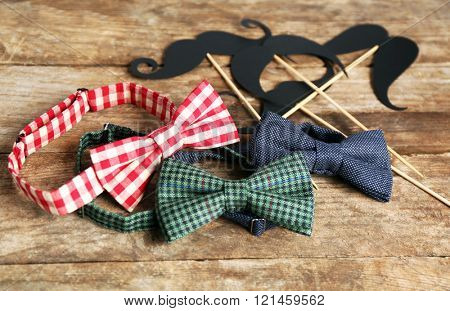 Different bow ties and mustache on wooden background