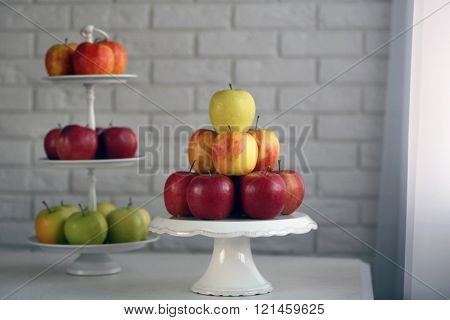 Ripe apples on stand on kitchen table