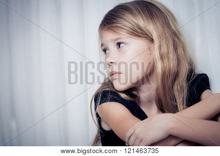 Portrait Of Sad Little Girl Sitting Near The Window At Home
