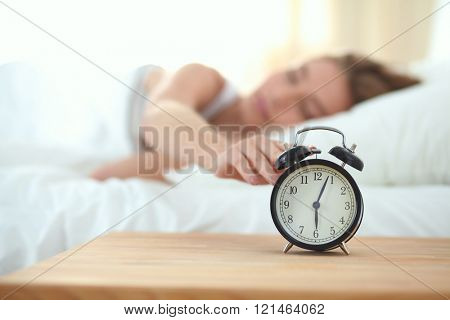 Young sleeping woman and alarm clock in bedroom at home