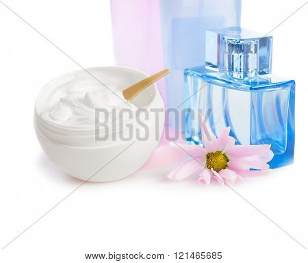 face cream in  white jar with pink flower and blue  glass vial  of toilet water on white background