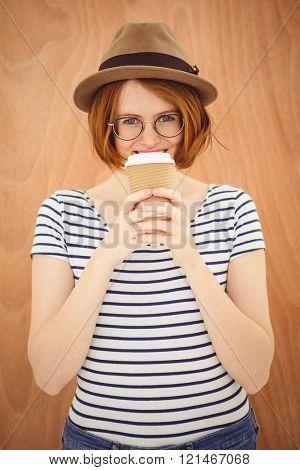 smiling hipster woman, wearing a trilby and drinking a cup of coffee