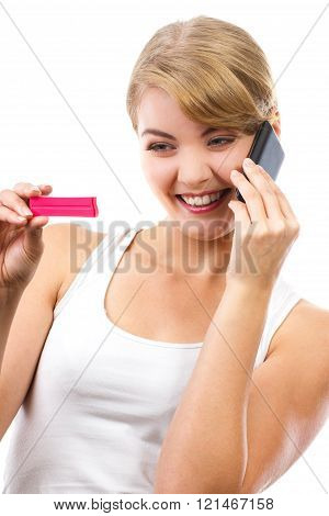 Happy woman with phone informing someone about positive pregnancy test