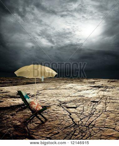 a deck-chair and beach umbrella on the desert