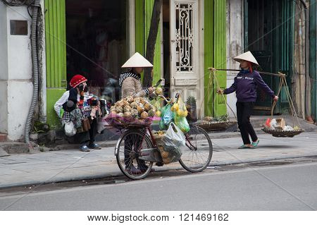 Vietnamese vendors with conical hat selling fruit