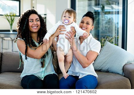 Lesbian couple playing with their baby in living room