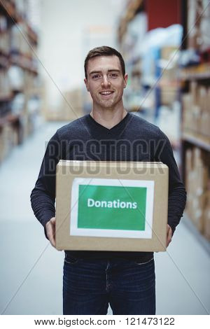 Volunteer smiling at camera holding donations box in warehouse