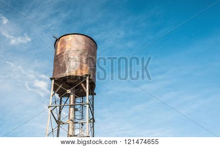 Old rusty water tank on the background of clear blue sky