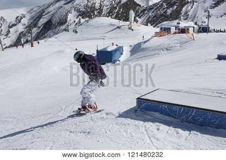 Young snowboarder woman sliding on a box.
