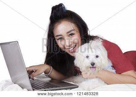 Cheerful model with dog and laptop on bed