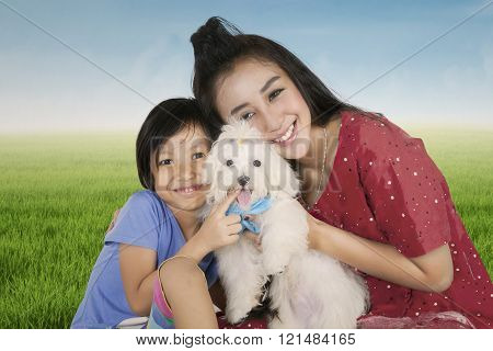 Happy mother and her daughter holding dog